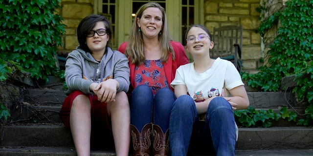 May 4, 2021: Heather Ousley, who plans to get her kids vaccinated as soon as they are eligible, sits with her older children Elliannah, 15, right, and Samuel, 13, in front of their home in Merriam, Kan.