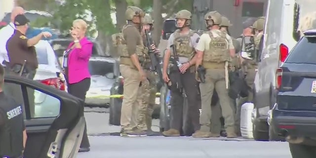 Authorities in Charles County, Md., gather amid a situation with a barricaded suspect who allegedly shot two officers Monday.