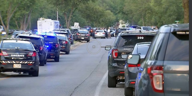 Charles County Sheriff's vehicles on a street near where two officers were shot Monday. The alleged gunman has barricaded himself inside a home, authorities said.