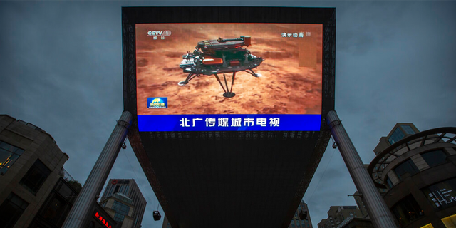 A Chinese state media broadcast of a news report about the country's successful landing of a probe on Mars is shown on a large video screen at a shopping mall in Beijing, Saturday, May 15, 2021.