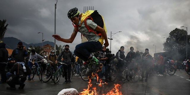 An anti-government demonstrator in skates jumps over a fire during a protest in Bogota, Colombia, Wednesday, May 5, 2021. The protests that began last week over a tax reform proposal continue despite President Ivan Duque's withdrawal of the tax plan on Sunday, May 2. (AP Photo/Ivan Valencia)