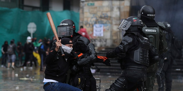 A protester clashes with the police during an anti-government protest in Bogota, Colombia, Wednesday, May 5, 2021. The protests that began last week over a tax reform proposal continue despite President Ivan Duque's withdrawal of the tax plan on Sunday, May 2. (AP Photo/Fernando Vergara)