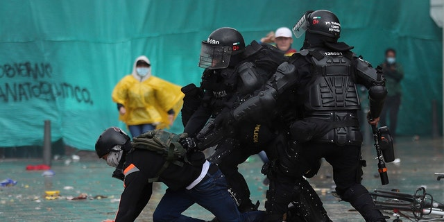 Police detain a demonstrator during an anti-government protest in Bogota, Colombia, Wednesday, May 5, 2021. The protests that began last week over a tax reform proposal continue despite President Ivan Duque's withdrawal of the tax plan on Sunday, May 2. (AP Photo/Fernando Vergara)