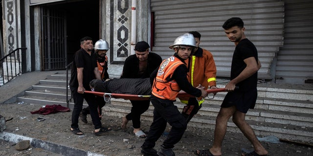 Palestinian rescuers evacuate an elderly woman from a building following Israeli airstrikes on Gaza City on Wednesday.