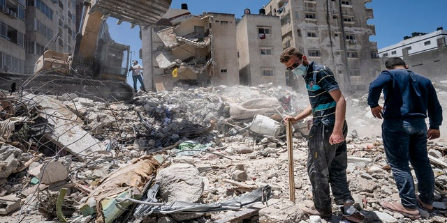 Heavy construction equipment is used to sift through rubble Thursday to uncover valuables before it is transported away from the scene of a building in Gaza City that was destroyed in a recent airstrike. (AP)