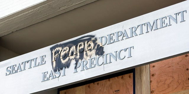 """The word """"people"""" is spray-painted over the word """"police"""" on the closed Seattle Police Department's East Precinct that was surrounded by the area known as the Capitol Hill Autonomous Zone (CHAZ), in Seattle last summer. (Getty Images)"""