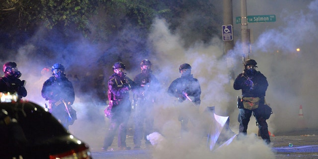 Security personnel stand in a cloud of tear gas in Portland, Oregon, early July 26, 2020. (Getty Images)