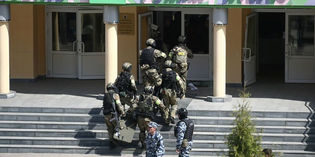Officers by the Russian school where two attackers reportedly opened fire on May 11, 2021. (Photo by Yegor AleyevTASS via Getty Images)