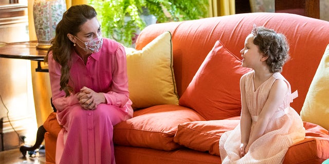 Catherine, Duchess of Cambridge meets Mila Sneddon, aged five, and her family, at the Palace of Holyroodhouse on May 27, 2021, in Edinburgh, Scotland. Cancer patient Mila features in an image from the Hold Still photography project which showed her kissing her father Scott through a window whilst she was shielding during her chemotherapy treatment.