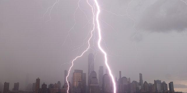 جرسی سیتی ، نیوجرسی - 6 جولای: همانطور که از جرسی سیتی ، نیوجرسی دیده می شود ، دو رعد و برق با برخورد به رودخانه هادسون در مقابل افق منهتن پایین در نیویورک هنگام طوفان در 6 جولای 2020 ، به یک مرکز تجارت جهانی برخورد می کند.  (عکس: گری هرشورن / گتی ایماژ)
