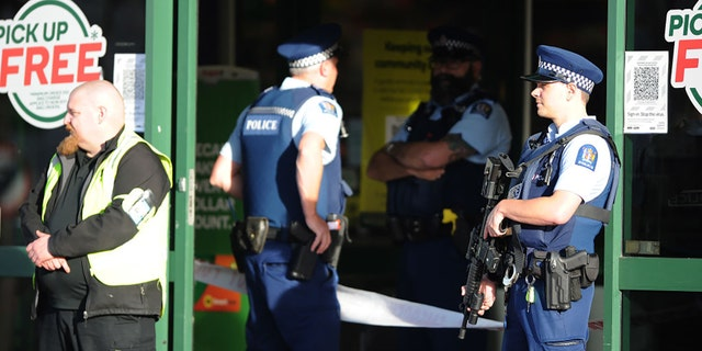 Police officers are observed standing guard outside the main entrance of the Dunedin Central Countdown on May 10, 2021, in Dunedin, New Zealand. (Photo by Joe Allison/Getty Images)