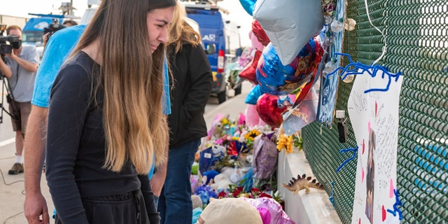 Alexis Cloonan, sister of 6-year-old Aiden Leos, cries at the memorial erected on freeway overpass in Orange, California, on Tuesday, May 25, 2021. (Getty Images)