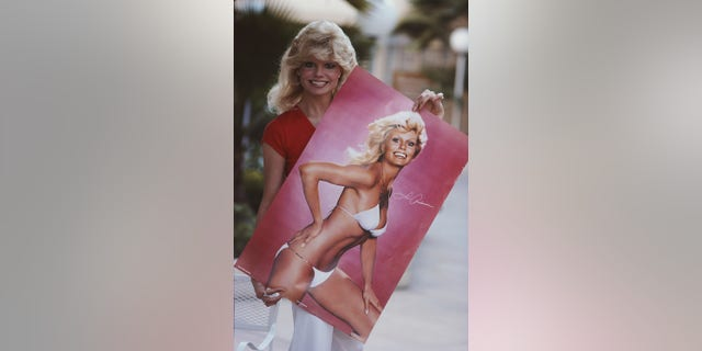 American actress Loni Anderson holds a poster of herself in a bikini, Los Angeles, circa 1979.