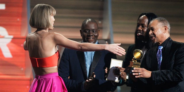 Singer Taylor Swift (C) accepts the Album of the Year award for '1989' onstage from musicians (L-R) Philip Bailey, Verdine White and Ralph Johnson of Earth, 風 &アンプ; Fire during The 58th GRAMMY Awards at Staples Center on February 15, 2016, in Los Angeles, カリフォルニア.
