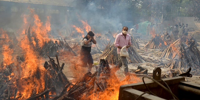 April 29, 2021: Relatives react to heat emitting from the multiple funeral pyres of COVID-19 victims at a crematorium in the outskirts of New Delhi, India.