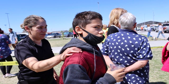 Adela Rodriguez, left, walks with her son, Yandel Rodriguez, 12, at the high school where people were evacuated after the shooting. (AP)