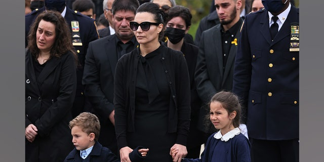 Irene Tsakos holds the hands of her children as she watches NYPD officers fold an American flag that draped the casket of her husband NYPD Officer Anastasios Tsakos during his funeral service at St. Paraskevi Greek Orthodox Shrine Church on May 04, 2021 in Greenlawn, New York.