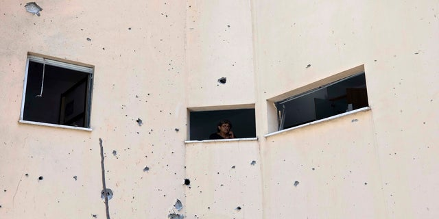 An Israeli woman looks out a window of her house at the site of a rocket attack in the central Israeli city of Petah Tikvah on Thursday. (AP)