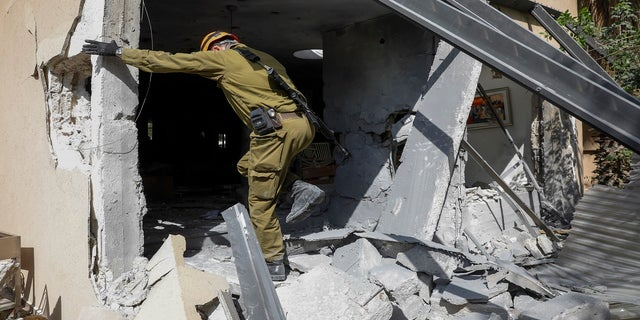 An Israeli soldier inspects a damaged house after it was hit by a rocket fired from the Gaza Strip, In Ashkelon, Israel on Thursday. (AP)