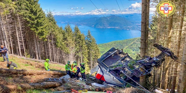 Rescuers work by the wreckage of a cable car after it collapsed near the summit of the Stresa-Mottarone line in the Piedmont region, northern Italy, on Sunday.