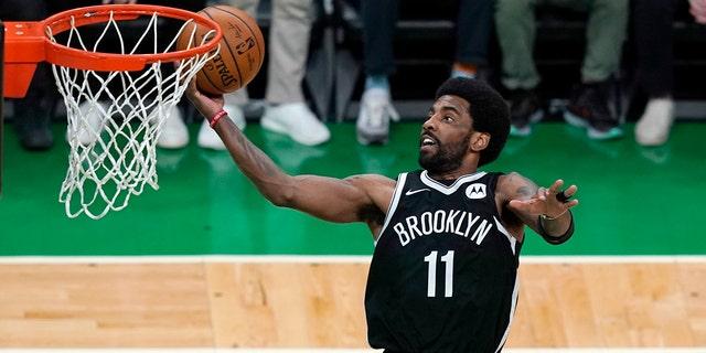 يسجل فريق Brooklyn Nets حراسة Kyrie Irving في الربع الأول من اللعبة 4 خلال إحدى مباريات الدور الأول في دوري كرة السلة NBA ، الأحد ، 30 مايو 2021 ، في بوسطن.