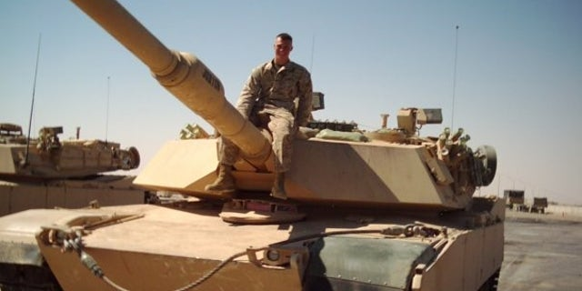 Private First Class Michael Logue on a tank