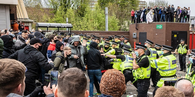 OLD TRAFFORD, MANCHESTER, UNITED KINGDOM - 2021/05/02: Police officers move in to disperse football fans during a protest against the Glazer's ownership of Manchester United.