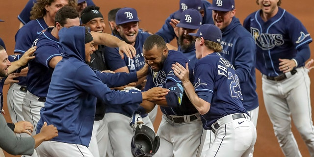 Tampa Bay Rays' Manuel Margot, center, is congratulated by teammates after his game-winning single against the Kansas City Royals during the 10th inning of a baseball game Wednesday, May 26, 2021, in St. Petersburg, Fla. The Rays won 2-1.
