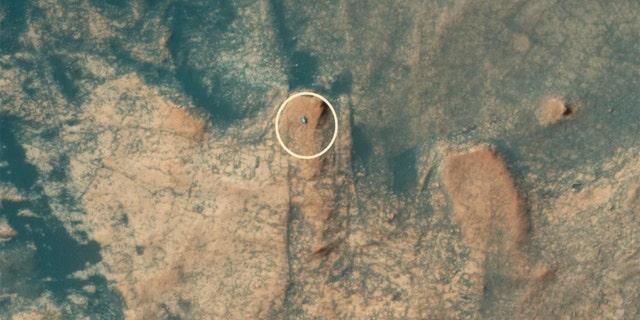 مریخ نورد کنجکاوی ناسا در یک تصویر هوایی که توسط دوربین HiRISE Mars Reconnaissance Orbiter (MRO) گرفته شده است ، از مارس مونت مرکو صعود می کند.  (اعتبار: NASA / JPL / دانشگاه آریزونا)