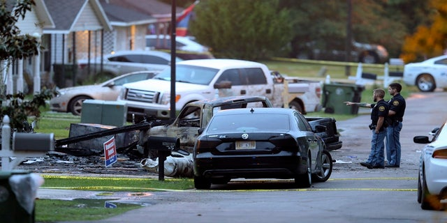 Hattiesburg police surround a burned automobile and a damaged home after a small plane crashed late Tuesday night in Hattiesburg, Miss. (AP/The Advocate)