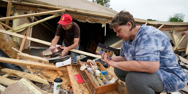 Vickie Savell, right, looks for her wedding band, as a friend and fellow church member pulls possessions from the remains of her new mobile home early Monday, May 3, 2021, in Yazoo County, Miss. Multiple tornadoes were reported across Mississippi on Sunday, causing some damage but no immediate word of injuries. (AP Photo/Rogelio V. Solis)