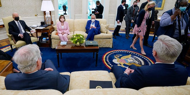 Members of the media are escorted out as President Joe Biden meets with congressional leaders in the Oval Office of the White House, 星期三, 可能 12, 2021, 在华盛顿. Clockwise from left, 拜登, 众议院议长南希·佩洛西, 参议院多数党领袖查克·舒默(Chuck Schumer), Senate Minority Leader Mitch McConnell and House Minority Leader Kevin McCarthy.