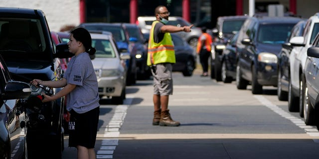 A customer pumps gas at Costco as a worker directs traffic on Tuesday in Charlotte, N.C. (AP)