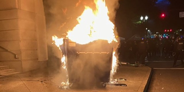 Marchers in Portland on Tuesday lit a dumpster on fire.