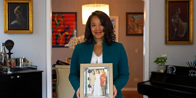 Robin Rue Simmons, alderwoman of Evanston's 5th Ward poses for a portrait holding a photograph of her mother, aunt and grandmother in her home in Evanston, Ill., Friday, April 9, 2021.