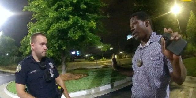 Rayshard Brooks (right) speaks to Officer Garrett Rolfe (left) in the parking lot of a Wendy's restaurant in Atlanta on June 12, 2020.  (AP / Atlanta Police Department)