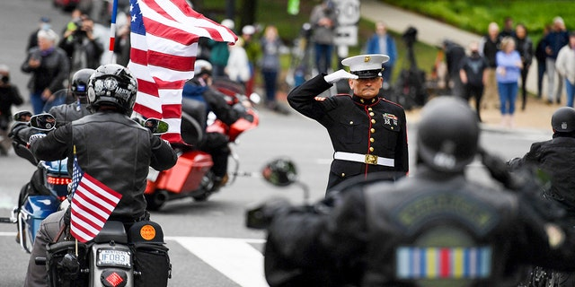 """Staff Sgt. Tim Chambers salutes as motorcyclists participate in the """"Rolling to Remember"""" demonstration as they ride past the Lincoln Memorial on May 30, 2021, in Washington, corriente continua. The event is to honor American prisoners of war and service members missing in action, and to call attention to veterans' issues. (OLIVIER DOULIERY/AFP via Getty Images)"""