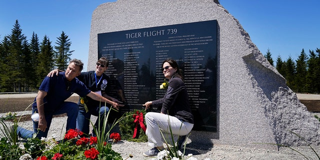 John Williams, of Peru, Indiana, left, and his sisters, Maria McCauley, of Branson, Missouri, center, and Susie Linale, of Omaha, Nebraska, pose at a monument to honor the military passengers of Flying Tiger Line Flight 739, Saturday, May 15, 2021, in Columbia Falls, Maine. Their father, SFC Albert Williams, Jr., was among those killed on the secret mission to Vietnam in 1962. (Associated Press)