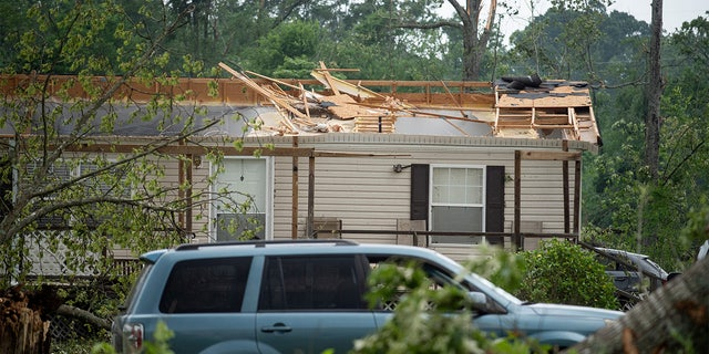 A roof of a home is missing on Ford Road in Byram, Mississippi, on Monday, May 3, 2021, after a tornado touched down in the area Sunday night.