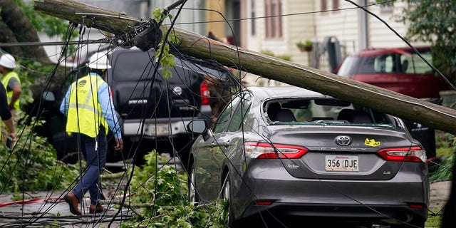 A downed power pole from a possible tornado sits on a damaged car after heavy storms moved through the area Tuesday night, in the Uptown section of New Orleans, Wednesday, May 12, 2021. (AP Photo/Gerald Herbert)