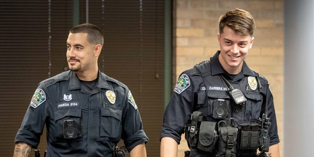 Mei 26, 2021; Austin, TX, VSA; Austin police officers Eddie Pineda, links, and Chandler Carrera arrive at a news conference at the Austin Police Department headquarters on Wednesday May 26, 2021, to speak about their experience of saving a man from a burning truck. (Jay Jannar-USA TODAY NETWORK)