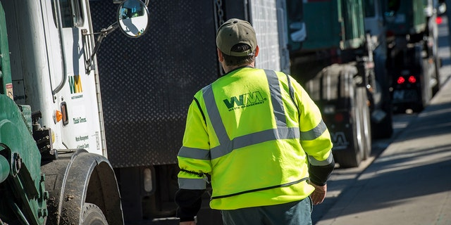 An employee walks toward a garbage collection truck in San Leandro, Calif., on Feb. 12, 2018.