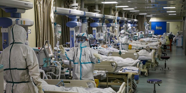 Medical workers in protective suits attend to novel coronavirus (COVID) patients at the intensive care unit (ICU) of a designated hospital in Wuhan, Hubei province, China, February 6, 2020.