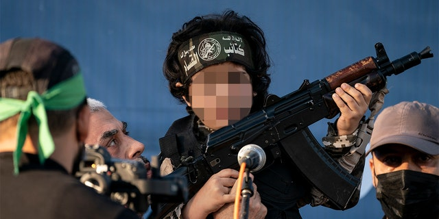 Yahya Sinwar, Palestinian leader of Hamas in the Gaza Strip, second left, holds a child in a soldier costume, on stage with a weapon for the cameras, at a rally of supporters days after a cease-fire was reached in an 11-day war between Gaza's Hamas rulers and Israel, Monday. (AP Photo/John Minchillo)