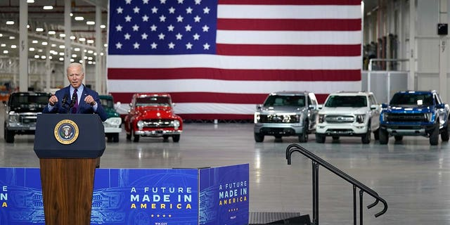 An electric F-150 Lightning (silver) was parked behind President Biden as he made remarks at Ford's Rouge Electric Vehicle Center.