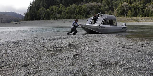 In this March 5, 2020, file photo, Hunter Maltz, a fish technician for the Yurok tribe, pushes a jet boat into the Klamath River at the confluence of the Klamath River and Blue Creek as Keith Parker, a Yurok tribal fisheries biologist, watches near Klamath, Calif. A severe drought is creating a water crisis not seen in more than a century for farmers, tribes and federally protected fish along the Oregon-California border as federal authorities cut off releases from a dam that provides critical sustenance for a massive irrigation project and bolsters downstream water levels for dangerously diminished salmon populations. (AP Photo/Gillian Flaccus, File)