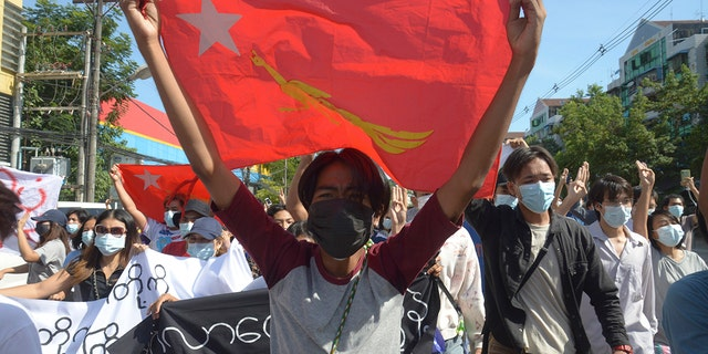 Anti-coup protesters show a National League for Democracy (NLD) party flag during a demonstration in Yangon, Burma, Friday May 14, 2021.  (AP Photo)
