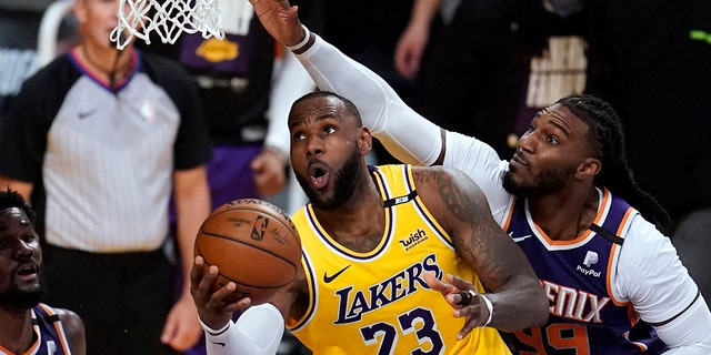 Los Angeles Lakers forward LeBron James, center, scores past Phoenix Suns forward Jae Crowder, right, during the second half in Game 3 of an NBA basketball first-round playoff series Thursday, May 27, 2021, in Los Angeles. (AP Photo/Marcio Jose Sanchez)