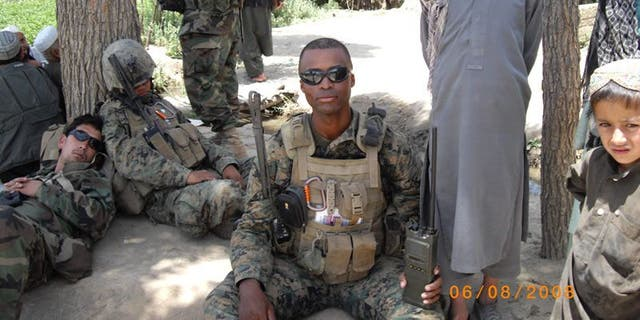 Jesse Melton III on active duty in Afghanistan in 2008, sitting alongside fellow Marines and Afghan children.