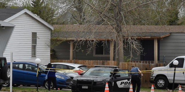 A Colorado Springs police officer goes to help a person who was in a different mobile home get to her car from behind the crime tape in Colorado Springs, Colo., on Sunday. A gunman opened fire at a birthday party in Colorado, slaying six adults before killing himself, police say. (AP/The Colorado Springs Gazette)